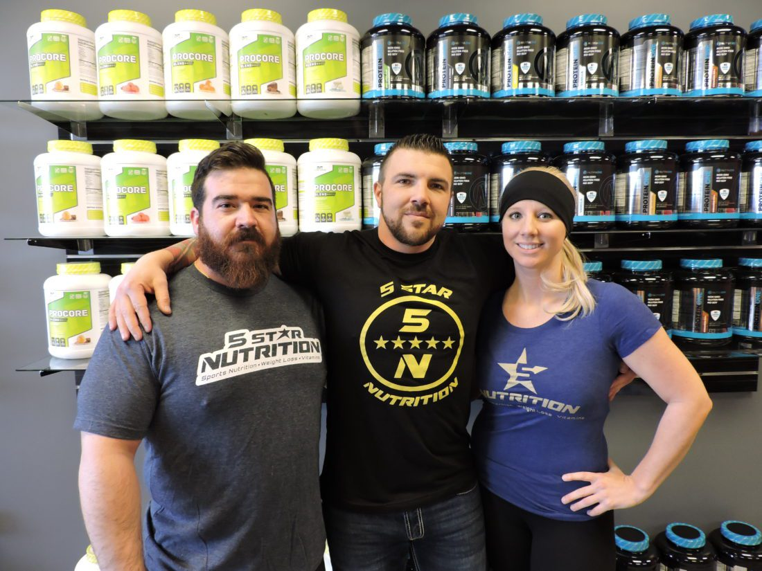 T-L Photo/JANELL HUNTER 5-Star Nutrition employees, from left, Josh Duncan, future store manager; Preston Parris, district manager; and Nichole Bizic, office manager, prepare for the store's grand opening at 10 a.m. Saturday.