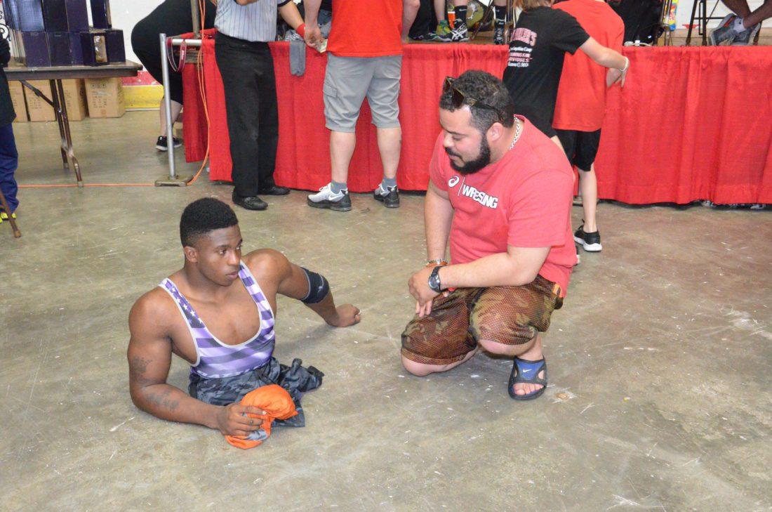 T-L Photo/KIM NORTH BELLAIRE GRADUATE Percy McGhee (right) talks with Zion Clark after a match at a tournament in Wheeling this past Sunday. Clark wrestles despite being born without legs.