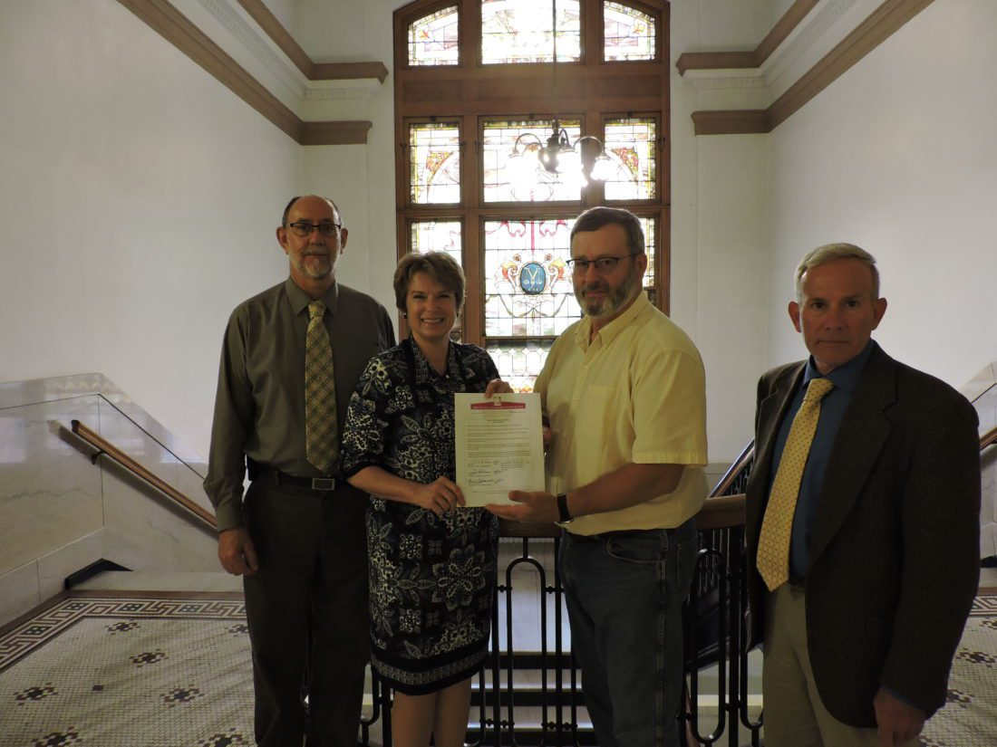 T-L Photo/JANELL HUNTER Monroe County Commissioner Carl Davis, from left, Mental Health and Recovery Board Executive Director Jayn Devney and Commissioners Tim Price and Mick Schumacher come together Monday to proclaim May as Mental Health Awareness Month.