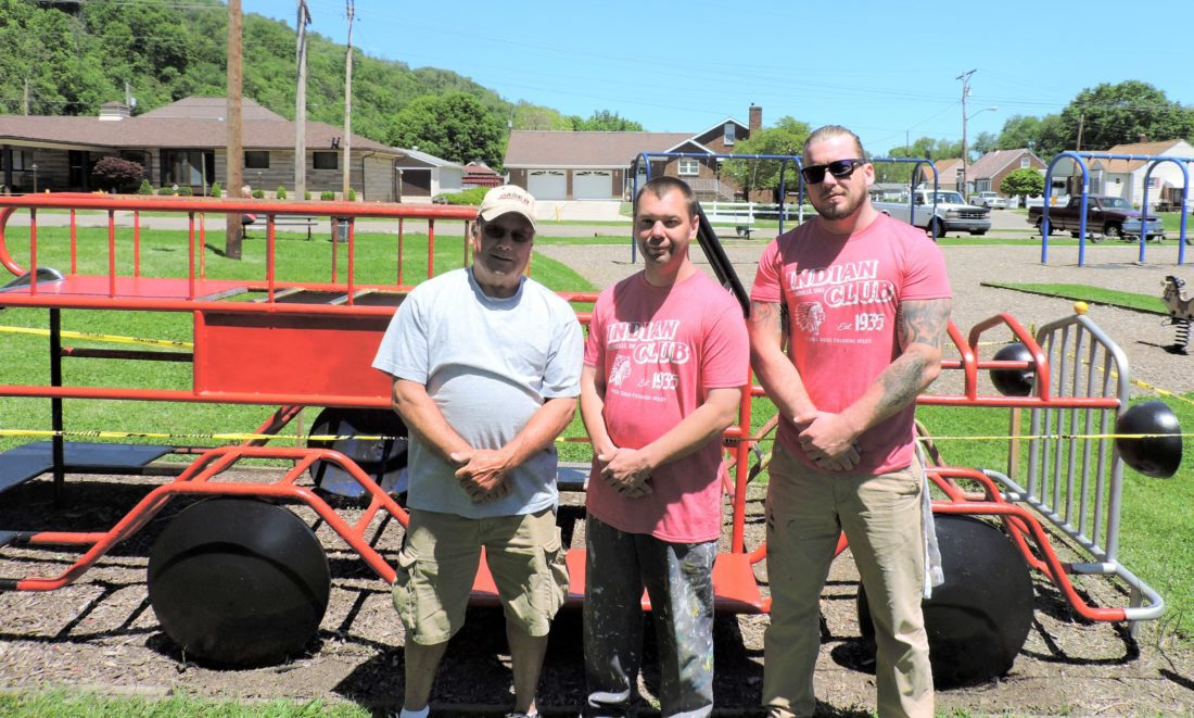 T-L Photos/DYLAN McKENZIE  WARREN TOWNSHIP Park manager Tom Schrader, left, stands with cousins Hank Kenjorsky, center, and Logan Taylor in front of a freshly painted fire truck play piece at the park. Taylor and  Kenjorsky spent much of Monday painting some of the aging and weathered play structures in the park.