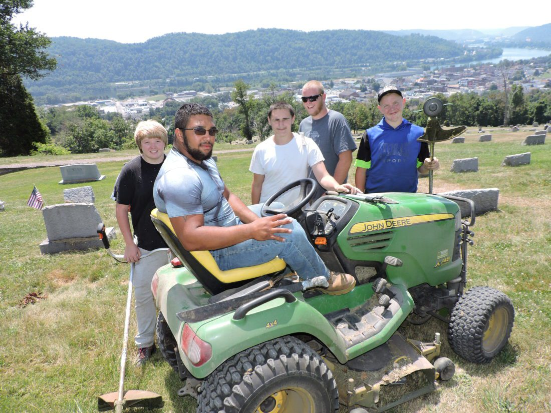 File Photo/SHELLEY HANSON TAKING a break, last summer, from their grass-cutting duties at Riverview Cemetery are, from left, Martins Ferry residents Logan Lovejoy; Tyus Harris (sitting on tractor); Preston Antill; and brothers Robert Brown and Chris Brown.