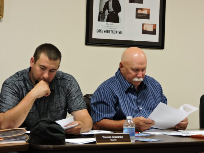 T-L Photos/DYLAN McKENZIE  Cadiz Village Council members Thomas Crawshaw, left, and Dan Ossman, fill out a survey at Thursday's meeting. Council members were asked to fill out a quick questionnaire regarding tobacco free outdoor spaces, both before and after listening to a speaker on the subject.