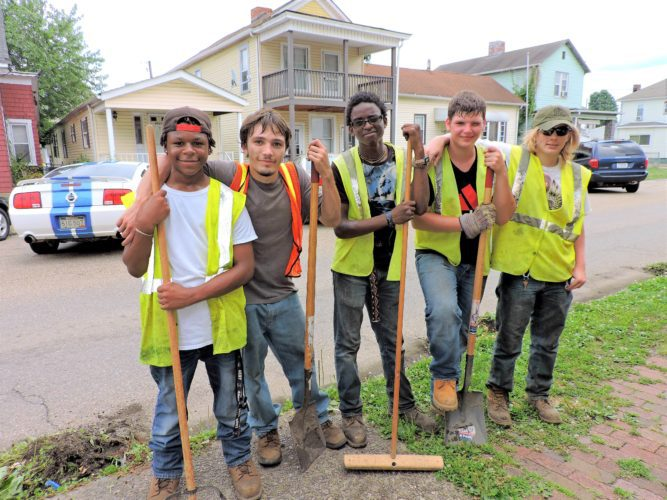 YOUTH WORKERS, from left, Maurel Irvin, 16; Michael Wise, 19; Quayvoughn James, 18; Bobby Landis, 18; and Matthew Schmidt, 18, take a break from cleaning curbs on Thursday on Noble Street in Bellaire.