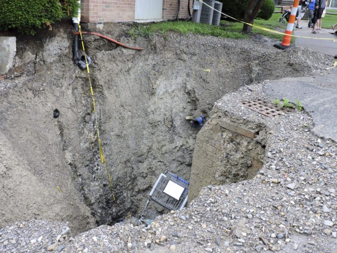 T-L Photo/DYLAN McKENZIE  A large sinkhole gapes open in front of Jaycee Manor Apartments in Martins Ferry. The hole, attributed to heavy rain, began to open around 3:30 p.m. Friday.
