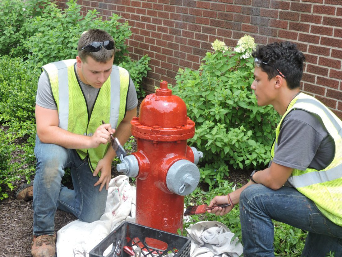 T-L Photo/ROBERT A. DEFRANK Joshua Robinson, left, and Daniel Trouten will be upgrading and painting the city of St. Clairsville's fire hydrants this summer. The hydrants will bear the city colors of red and gray. Aaron Kerner, who was not present for the photo, will be helping as well.