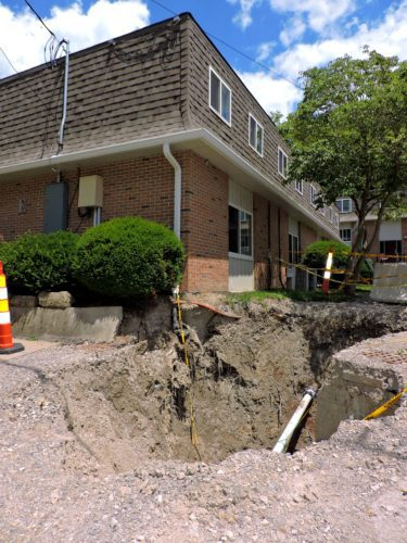 T-L Photo/SHELLEY HANSON A LARGE sinkhole gapes open in front of the Jaycee Manor Apartments in Martins Ferry on Monday. The contractor who did work there previously is expected to fix the situation at no extra cost to the city.
