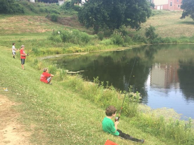 Photo Provided  Children fish in the lake at Olney Friends School in this photo taken from the Belmont Soil and Water Conservation District Facebook page. The SWCD is holding a Passport to Fishing event on July 12 to help teach aspiring anglers about fishing in Ohio.