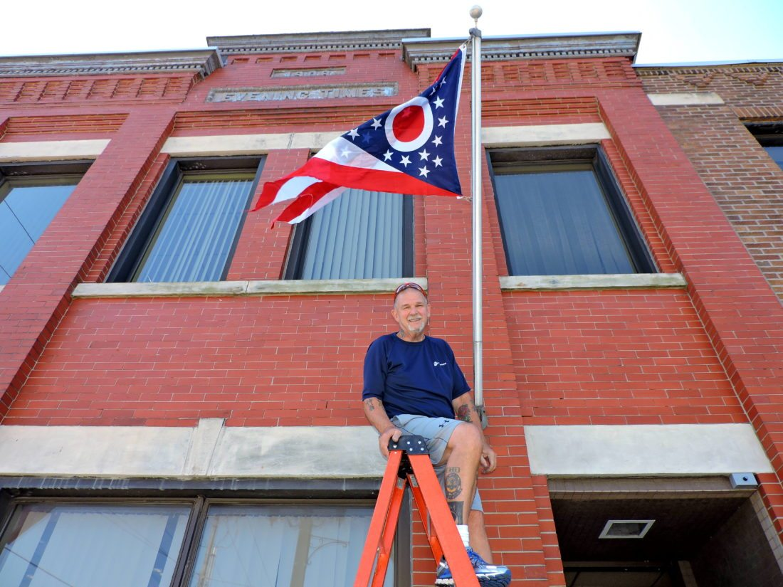 T-L Photo/SHELLEY HANSON TERRY WILDMAN, a Vietnam war veteran, sits atop a ladder after installing a new state of Ohio flag at The Times Leader office on Fourth Street in Martins Ferry on Tuesday. He also installed an American flag on another pole at the building. The flags were donated by the Bellaire VFW Post 626.