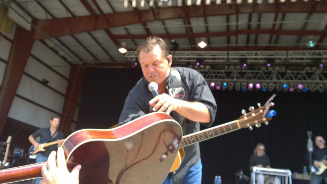 T-L Photos/JENNIFER COMPSTON-STROUGH Country music star Sammy Kershaw signs a guitar held up by a fan in the crowd at Jamboree In The Hills. The lucky owner of the guitar was Tim Lucas of Barnesville.