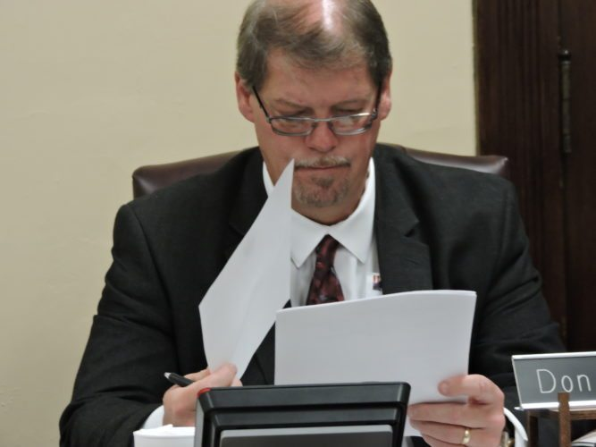 T-L Photo/DYLAN McKENZIE/ Harrison County Commissioner Don Bethel reads over a resolution at Wednesday's meeting. Commissioners approved a second reading of a request by the Harrison County Council on Aging for a levy renewal.