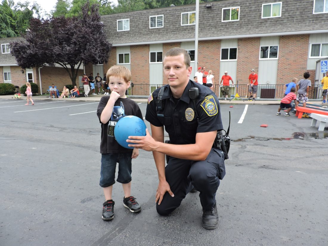 T-L Photo/JANELL HUNTER Martins Ferry Police Officer Shamus Nixon plays ball with 4-year-old Braxton Hall at a Jaycee Manor Crime Watch/Martins Ferry Police Department community event on Friday.See related photo on page A2.