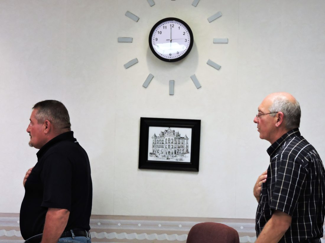 T-L Photo/SHELLEY HANSON/ BELLAIRE MAYOR Vince DeFabrizio, left, and Clerk Tom Sable recite the pledge of allegiance during council's regular meeting. On the wall in the background is a clock containing a hidden camera that has caused controversy.