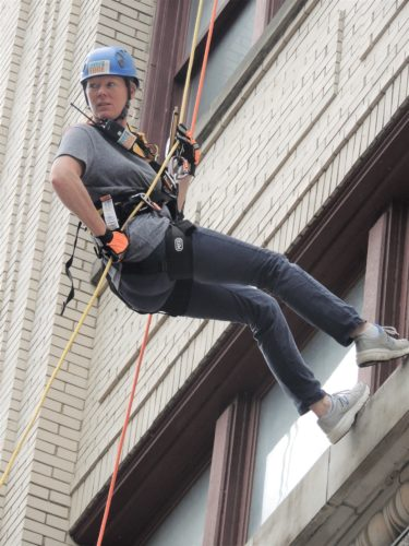 File Photo/ Tammy Kruse, director of development at Youth Services System, rappels down the Stone Center during the Wheeling YWCA's Over the Edge event last year.