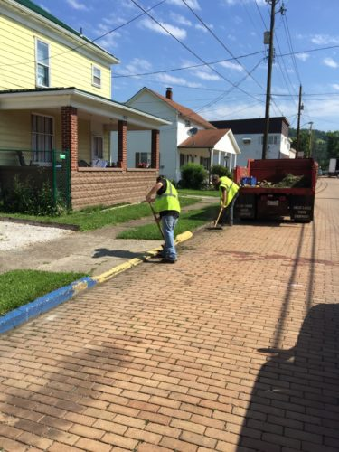 Photo Provided Community service workers sweep streets in Tiltonsville as part of a Jefferson County Court system program that allows defendants to work off their court costs and fines.