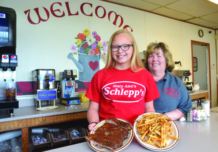 Photo by Scott McCloskey  Displaying an order of their homemade ribs and french fries is Schlepp's Family Restaurant Owner Maryann Lucas, at right, with her granddaughter Rilee Lucas.