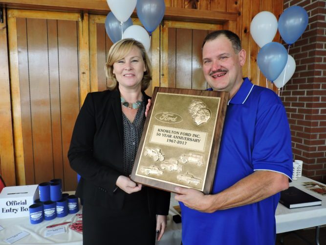 T-L Photo/JANELL HUNTER Megan Carlini of the Ford Motor Company presents a 50-year award to Mike Knowlton, owner of Knowlton Ford in Woodsfield.