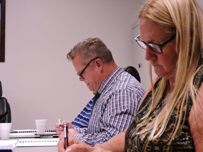 T-L Photo/ ROBERT A. DEFRANK Martins Ferry City Schools Superintendent Jim Fogle and Treasurer Karen Blake review business during Monday's board of education meeting.