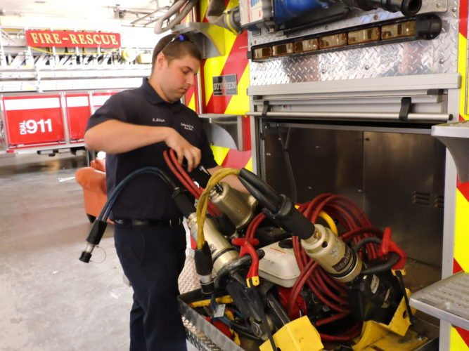 Firefighter Michael Minder shows a hydraulic spreader, one of the tools used to extricate people from auto accidents.