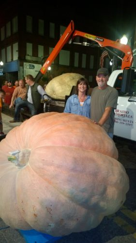 T-L Photo/JENNIFER COMPSTON-STROUGH Todd and Donna Skinner of Barnesville are dwarfed by the 2,150-pound gourd they grew to capture the title of King Pumpkin on Wednesday.