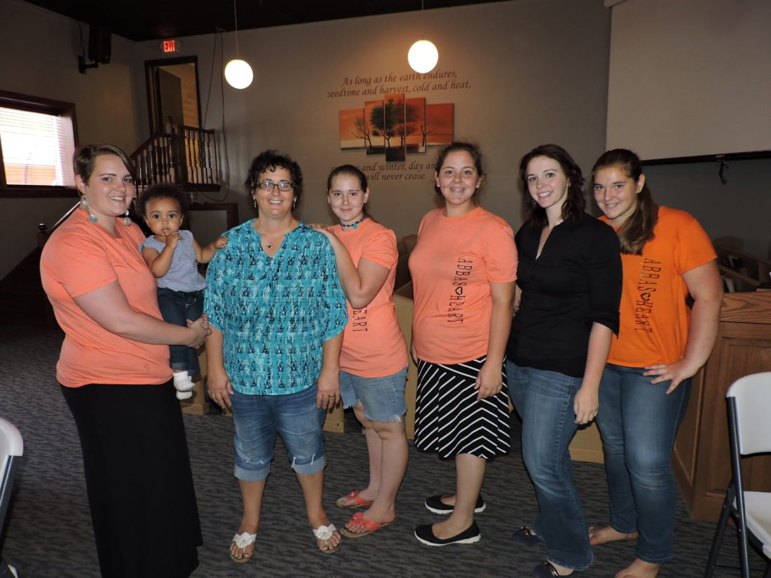 T-L Photo/SHELLEY HANSON Martha Hershberger, second from left, poses with some of her children at Shekinah Fellowship in downtown Barnesville on Friday. From left are Katie Kasoh holding her daughter Zuri; Hershberger; Hannah, 11; Krista, 15; Leona; and Kara, 13
