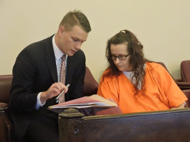 Lola Eden and defense attorney Adam Myser review Eden's case before she entered a guilty plea to trafficking in drugs on Friday.     T-L Photo/ROBERT A. DEFRANK