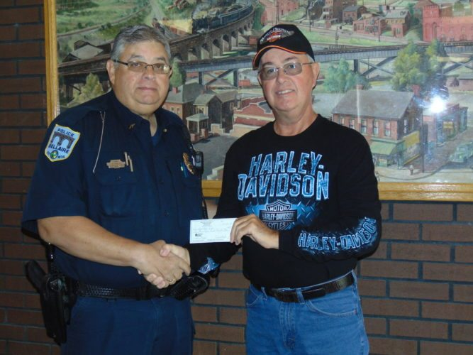 Photo provided BELLAIRE POLICE Chief Mike Kovalyk, left, receives a donation check from Eagles officer Danny Hughes for the department to upgrade its tactical equipment.  Bellaire Police receive donation for tactical equipment upgrade