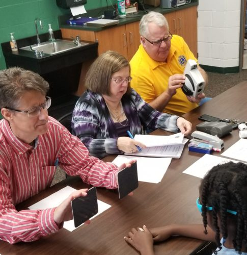 Photo provided MARTINS FERRY Lions Club members, from left, Bill Tolbert, Pam Stecker and Mike Yeso conduct eye screenings on Ayers Elementary School's fourth-grade students this week.  Martins Ferry Lions conduct eye screenings at school