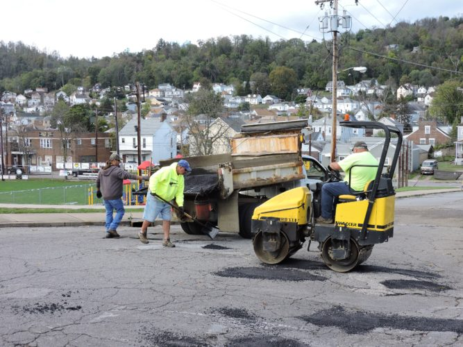 T-L Photo/SHELLEY HANSON/ MARTINS FERRY city street department employees, from left, John Russell, Bill Joe Snyder and Chris Hall work to patch potholes on Hickory Street on Monday afternoon.