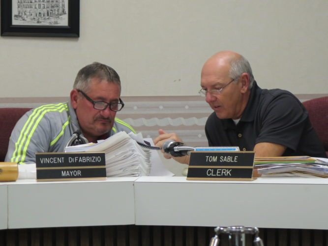 Bellaire Mayor Vince DiFabrizio, left, and Clerk/Treasurer Tom Sable confer during the Bellaire Village Council meeting Thursday.
