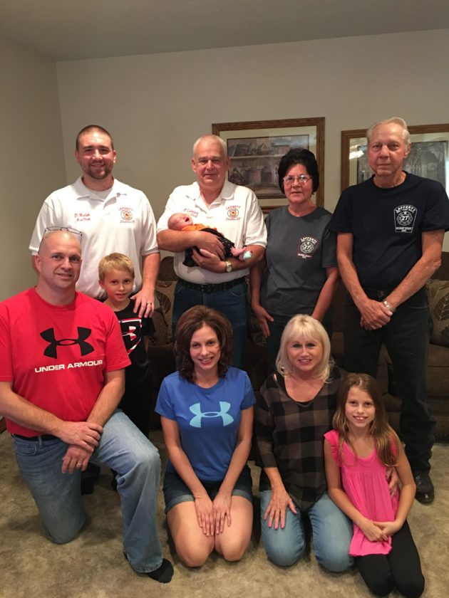 Photo provided MEMBERS OF the Lafferty Volunteer Fire Department's emergency squad visit newborn Katie Kildow at her home in Belmont. The squad delivered the baby on Sept. 27. Standing from left are Assistant Fire Chief Dustin Hudak, Fire Chief Larry Zalesny, holding baby Katie, EMT Diane Hudak, and e-squad driver Jim Garrett. In front are father Shane Kildow, brother Luke Kildow, mother Patty Kildow, grandmother Carol Lewis and sister Taylor Kildow.