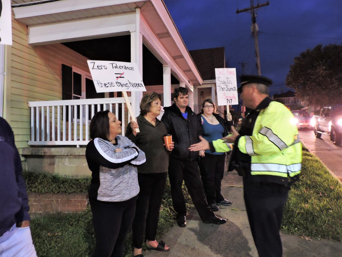 T-L Photo/SHELLEY HANSON/ ST. CLAIRSVILLE Police Chief Jeff Henry, right, talks with a group of people protesting outside of St. Clairsville High School about 6:45 a.m. this morning. The protest is related to the alleged sexual assault of a fifth grade student during a football game on Oct. 13.
