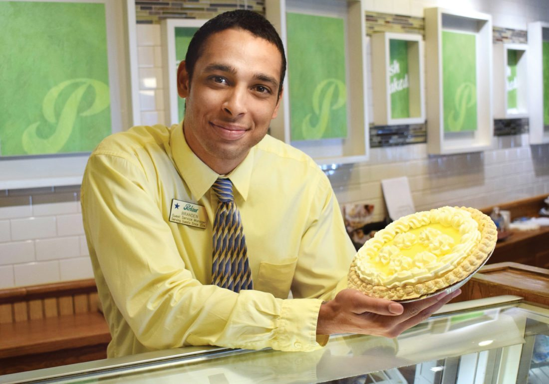 Photo by Scott McCloskey  Perkins Restaurant & Bakery Guest Service Manager Branden Womack displays their lemon supreme pie in the lobby of the Wheeling store.