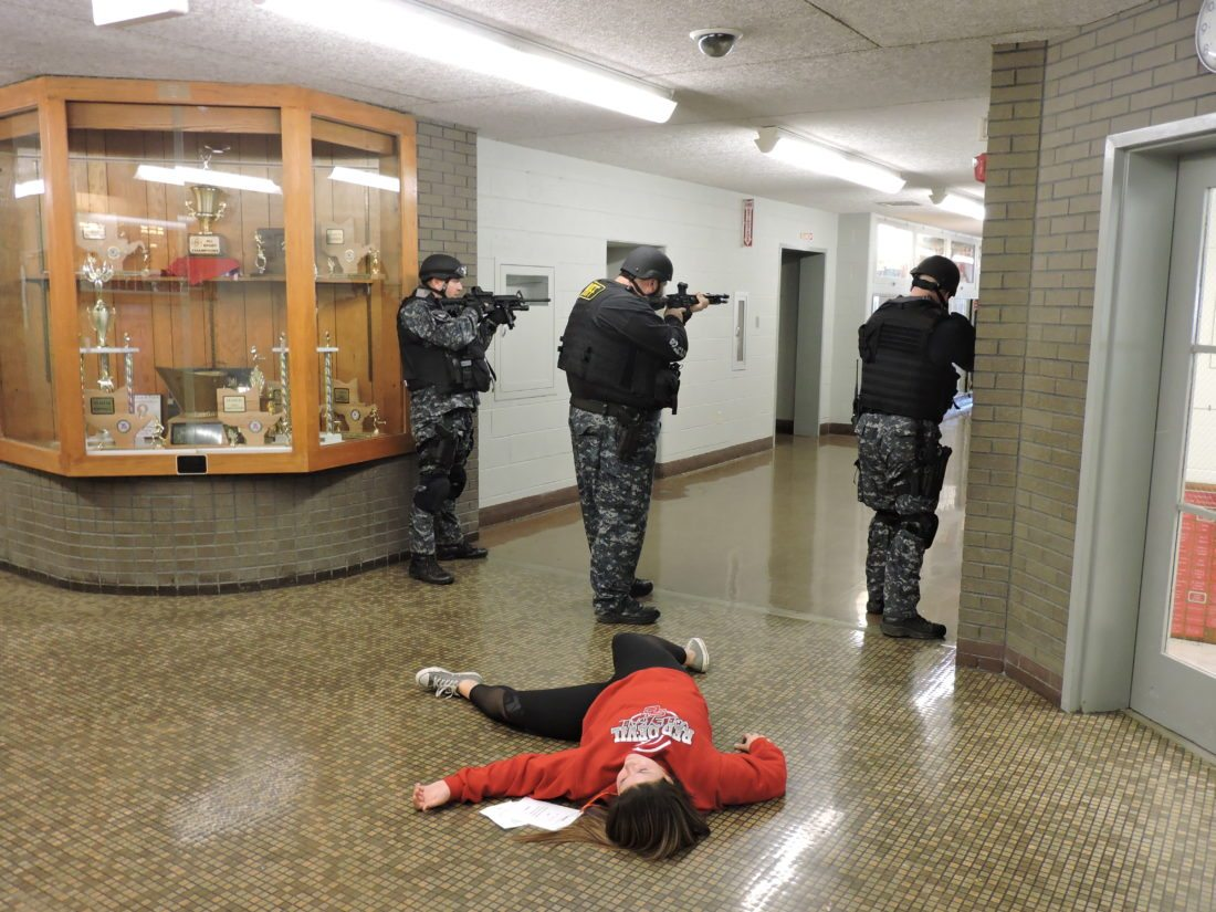 """T-L Photos/DYLAN McKENZIE  Members of the Belmont County Sheriff's Office Special Operations branch guard an """"injured"""" student during Thursday's active shooter training drill. Officers secured the building so that EMS personnel could move in and treat the simulated injuries of students."""