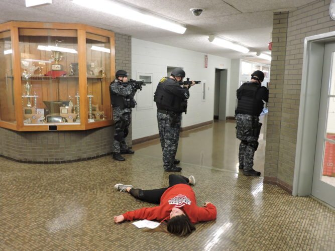 "T-L Photos/DYLAN McKENZIE  Members of the Belmont County Sheriff's Office Special Operations branch guard an ""injured"" student during Thursday's active shooter training drill. Officers secured the building so that EMS personnel could move in and treat the simulated injuries of students."