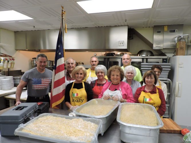 T-L Photo/DYLAN McKENZIE  Volunteers with the Sons of Italy in Bellaire pose with the food served to veterans at a spaghetti dinner on Friday evening. The Sons of Italy annually serves the food to veterans and their immediate families. Shown in the front row, from left, are Belmont County Common Pleas Judge Frank Fregiato, lodge President Doug Hartlieb, Courtney Hartlieb, Gilda Reed and Dianne Giannangeli. Middle row, from left, Rosalind Fitch, Lotus Bumgardner and Theresa Mowery. Back row, from left, David Badia and Mike Dossie.