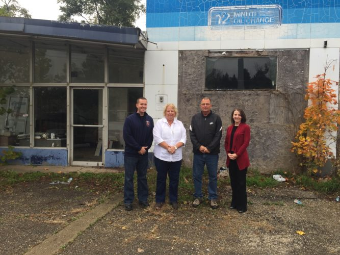 Photo provided Belmont County and Richland Township officials stand in front of a dilapidated former gas station beside Ohio 9 before it was demolished last week. Shown from left are Tim Hall, Richland Township fire prevention officer; Cindi Henry, Richland Township fiscal officer; Greg Reline, Richland Township trustee; and Kathy Kelich, Belmont County treasurer.