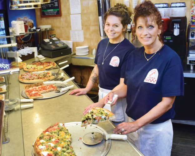 Photo by Scott McCloskey  Fabio's Pizza manager Candy Basil, right, and Haleigh Hannas wait on customers at the restaurant's front counter.