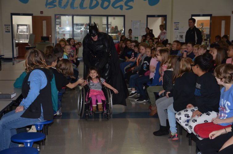ABOVE: BATMAN PUSHES Bridgeport first-grader Karlee Bowers in her wheelchair prior to an assembly for elementary school students Friday morning. Batman, along with Wonder Woman, talked about bullying and what to do if you know a bully or see someone bullying someone else.