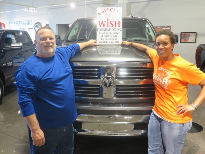 Robert Thomas, owner of Thomas Auto Center, left, and Alicia Freeman, executive director of A Special Wish Foundation, right, pose for a photo.      Photo by Alec Berry