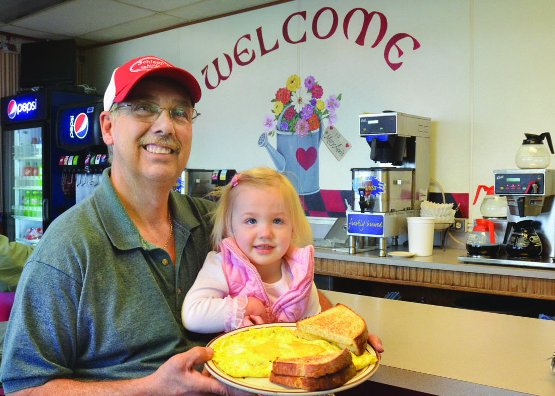 Photo by Scott McCloskey  Rusty Lucas of Bethesda holds his granddaughter Raelyn Lucas while displaying one of Schlepp's Family Restaurant's three-egg cheese omelettes.