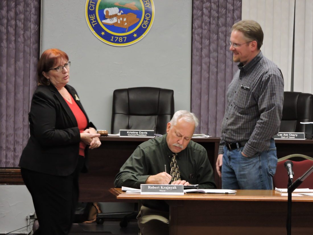 T-L Photo/SHELLEY HANSON MARTINS FERRY Mayor Robert Krajnyak, center, signs paperwork as Council President Kristine Davis and Service Director Chris Cleary talk before Wednesday's City Council meeting.