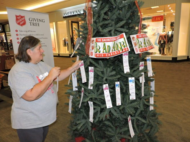 T-L Photo/SHELLEY HANSON VOLUNTEER ALICE Silva adjusts Angel tags on the Belmont County Salvation Army's Giving Tree at the Ohio Valley Mall in St. Clairsville. There are still children who need sponsored. The tags and gifts are due back Dec. 19.