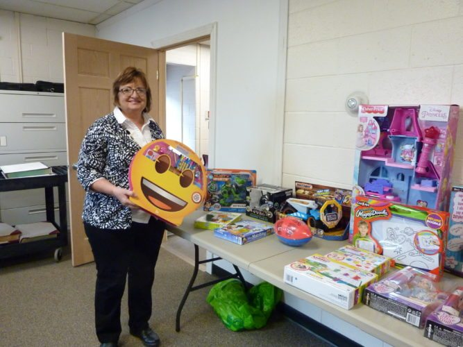 Photo by Linda Comins Linda Mehl, Belmont County director of nursing, shows new toys donated by health department employees for the Belmont County Commission's holiday toy drive for children in need. The health workers have purchased $200 worth of games and toys for this year's effort.