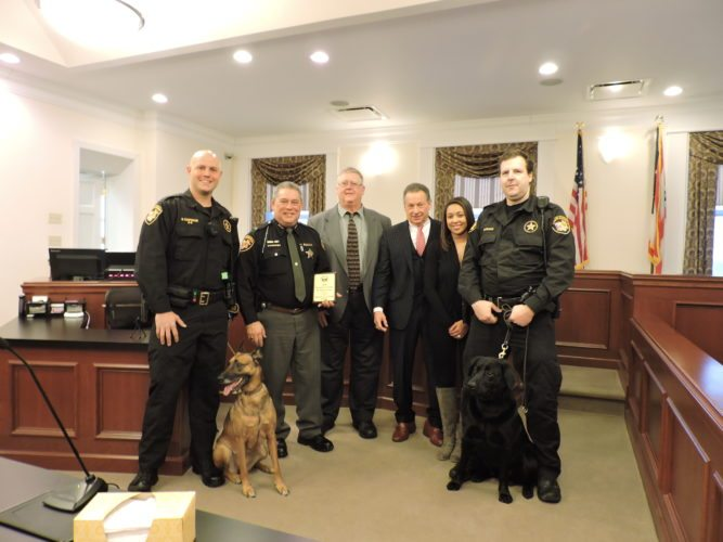 Officials from around Belmont County stand for a picture after Belmont County Auditor Roger Conroy awarded the first dog registration tag of 2018 to K-9 Copper of the Belmont County Sheriff's Department. From left are K-9 handler Deputy Brian Carpenter and his partner, Hyra, Sheriff Dave Lucas, Conroy, Common Pleas Judge Frank Fregiato, auditor's clerk Brianna Vaughn and K-9 handler Deputy Jason Schwarck and his partner, Copper.