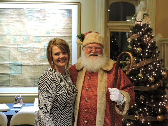 Barb Ballint, executive director of the Belmont County Tourism Council, poses with Santa Claus at the council's open house Thursday at the Belmont County Sheriff's Residence Museum. The event gave the chance for business owners and groups around the county to mingle.