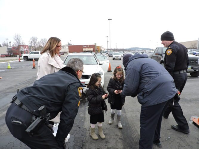 "Photos by Heather Ziegler Tina Catalano of Martins Ferry and her daughters, Briella, 5, left, and Malena, 7, are thanked for donating to the Operation Toy Lift project by officers, from left, Wheeling Police Sgt. Gregg McKenzie, Wheeling firefighter Watson ""Bob"" Bartsch and Police Chief Shawn Schwertfeger."
