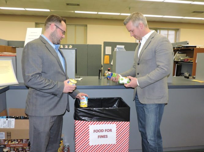 Photo by Casey Junkins Wheeling Vice Mayor Chad Thalman, left, and Mayor Glenn Elliott count some of the canned food donations the city is collecting in lieu of $10 parking ticket fines on Friday in the Finance Department office.