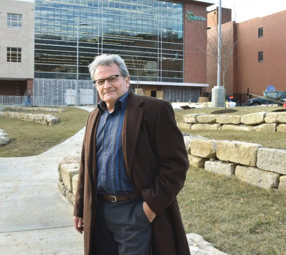 Photo by Scott McCloskey  Victor Greco, principal architect with the Mills Group, stands near the large stones — once part of an underground vault — that have been repurposed for use in the outdoor plaza at The Health Plan's new headquarters in downtown Wheeling.