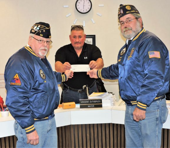 T-L Photo/SHELLEY HANSON BELLAIRE MAYOR Vince DiFabrizio, center, receives a $2,000 check for the village from American Legion Post 52 members Bill Wilson, left, and Dick Johnson during village council's regular meeting on Thursday. The post members gave the money to help the village pay for needed work truck repairs.