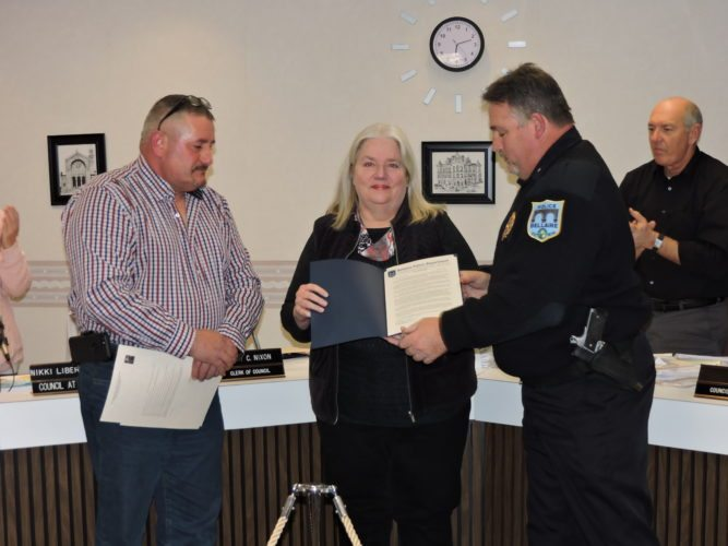 """T-L Photo/SHELLEY HANSON LT. DONNA Baroch, center, is thanked for her service during Thursday's Bellaire Village Council meeting by Acting Police Chief Richard """"Dick"""" Flanagan, right, and Mayor Vince DiFabrizio. She retired after 36 years on the force."""